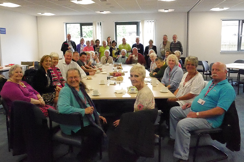 A group of volunteers enjoying tea and cake at their tea party.